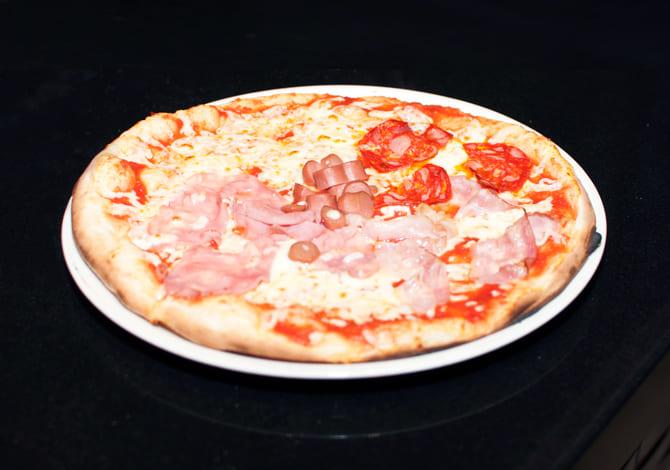 Pizza capricciosa <small>(tomate, mozzarella,  jamón york, alcachofas,champiñones, salchichas, aceitunas negras, aceite y orégano)</small>